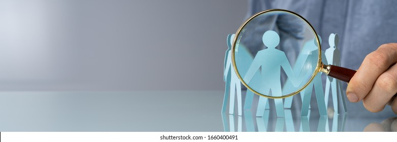 Holding Magnifying Glass And Paper People. Closeup Shot