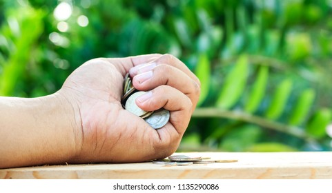 Holding many coins in the hand on the floor. Save money and use it for investment for your future.