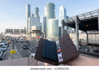 Holding opened purse with phone and credit cards. Business concept. Moscow City International Business Center with a highway at the background on sep. 10 2018 - Moscow, Russia