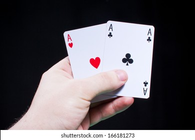 Holding a pair of aces on black background in studio.