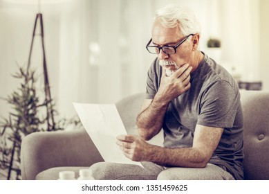 Holding papers in hands. Elderly grey-haired gentleman wearing glasses and grey t-shirt sitting on sofa and holding papers in hands