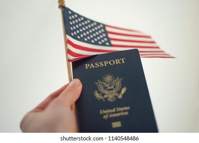 Holding Passport of USA and American flag in left hand, white background.