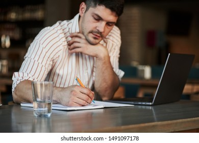 Holding pen and writing stages of project. Adult man sits in cafe at daytime and using the laptop for the remote work.