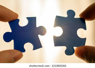 holding piece of blue jigsaw puzzle. idea, sign, symbol, concept of connecting business strategy. against sun rays sunset