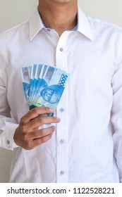 Holding pile of fifty thousand Indonesian Rupiah using one hand