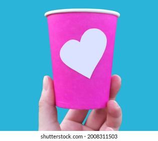 Tenant une tasse de café rose avec un autocollant en forme de coeur vierge. Main tenant une image de tasse en papier isolée sur fond clair. L'endroit en forme de coeur vide pour votre conception.