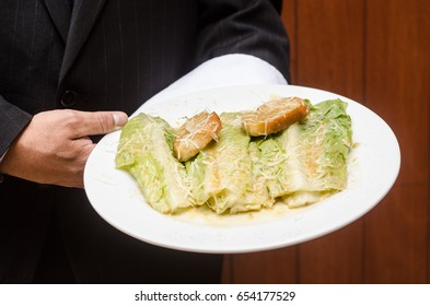 holding a plate of caesar salad, restaurant food