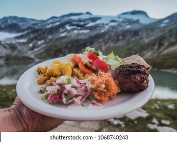 holding a plate full of fresh and tasty food outdoor with a great mountain view in the alps