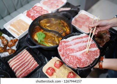Holding raw sliced beef using chopsticks on japanese hot pot with smoke, prepared for shabu shabu or Sukiyaki.