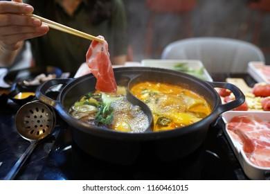 Holding raw sliced pork using chopsticks on hot pot with smoke for Japanese hot pot also known as Shabu Shabu or Sukiyaki is Japanese style.