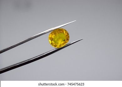 Holding a real/ natural raw (uncut) yellow diamond/ gem stones, with stainless steel tweezers