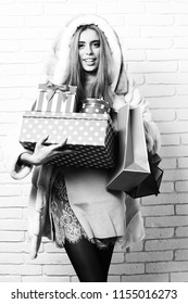 88fd9522e47 holding red big presents or gifts with pegs on brick wall studio  background. young fashionable