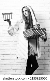 64d97f4d308 holding red big presents or gifts on brick wall studio background. young  fashionable sexy pretty