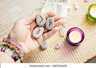Holding rune stones in hand. Candles burning on light wooden background.