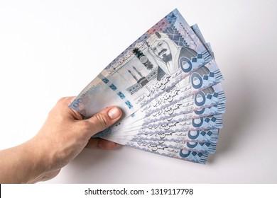 Holding Saudi riyals banknotes by hand