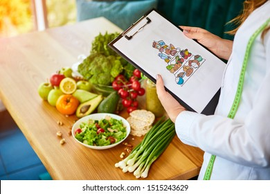 Holding schematic meal plan for diet with various healthy products on the background. Weight loss and right nutrition concept. Eating food pyramid