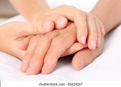 Holding senior hand, giving help