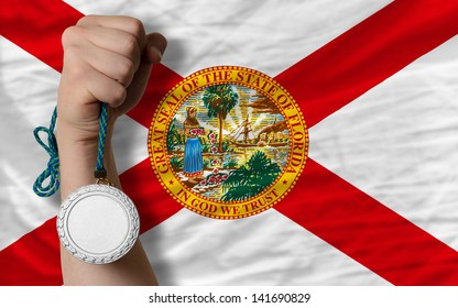 Holding silver medal for sport and flag of us state of florida