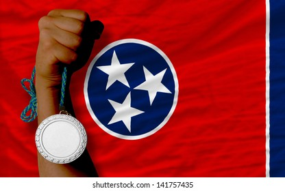 Holding silver medal for sport and flag of us state of tennessee