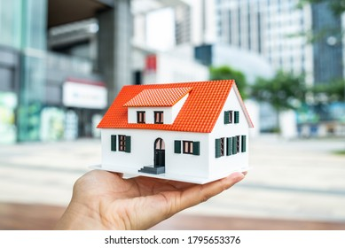 Holding a small house model in the community