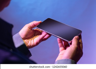 Holding smarthphone with both hands. Mobile phone for business concept. Isolated on blue background.