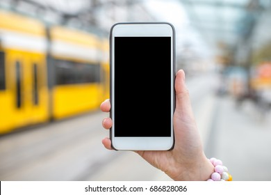 Holding a smartphone with empty screen on the modern tram stop background