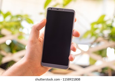Holding a smartphone on hand with a blank black screen