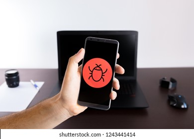 Holding a smartphone on hand with a bug sign logo