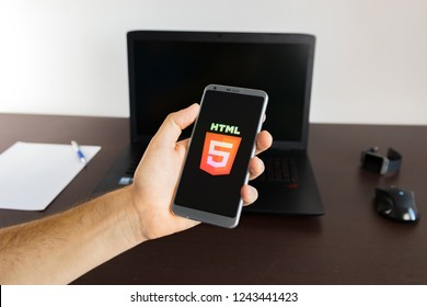 Holding a smartphone on hand with a HTML5 sign logo