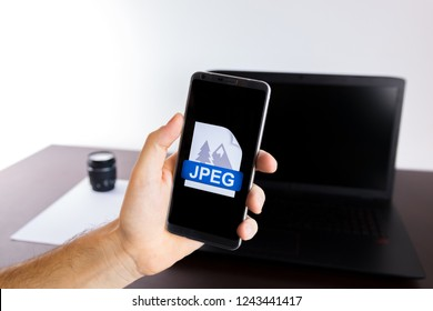Holding a smartphone on hand with a JPEG sign logo