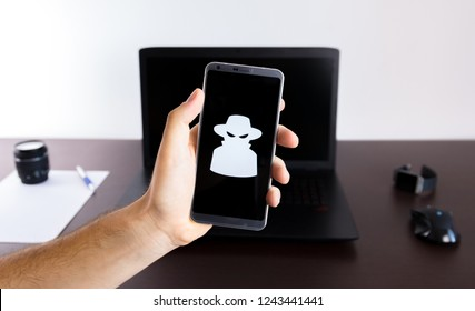 Holding a smartphone on hand with a spy sign logo