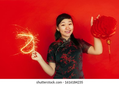 Holding sparkler and lantern. Happy Chinese New Year 2020. Asian young girl's portrait on red background. Female model in traditional clothes looks happy. Celebration, emotions. Copyspace.
