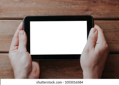 Holding tablet device over wooden table. Empty copy space white screen.