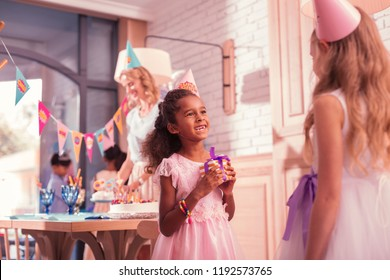 Holding tiny present. Pretty little girl smiling and feeling glad while holding a little present for her best friend
