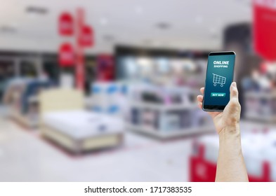 Holding a touch screen smartphone with online shopping word on a shopping mall background.