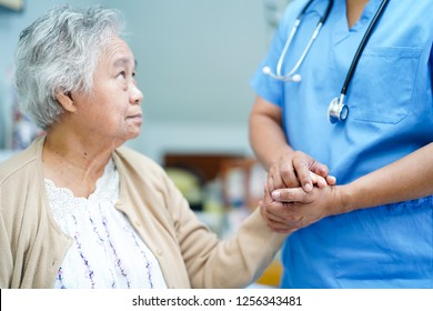 Holding Touching hands Asian senior or elderly old lady woman patient with love, care, helping, encourage and empathy at nursing hospital ward : healthy strong medical concept