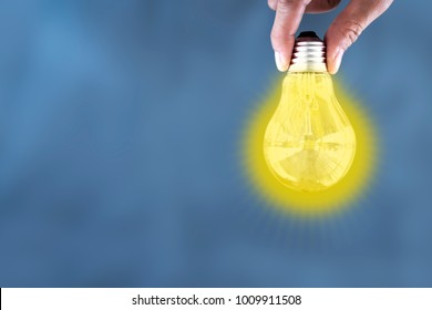 Holding turn on  light bulb on blue background ,with light blub concept.