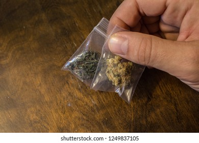 Holding two bags of different medical marijuana.