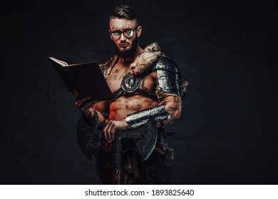 Holding two handed axe on his shoulder nordic fighter weared with glasses poses in dark background with book.