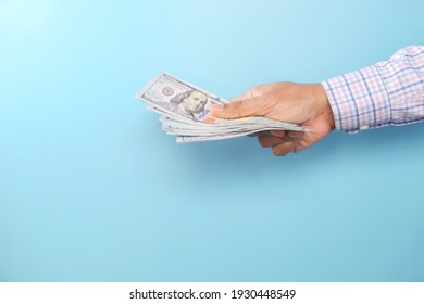 holding us dollar cash against blue background with copy space