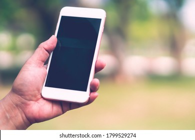 Holding and use smart mobile phone to communication at outdoor in park.