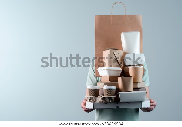 Çeşitli paket yiyecek kapları, pizza kutusu, kahve fincanları tutucu ve kağıt torbasında, yakın çekim. Açık gri arka plan, metin eklemek için yer. Teslimatçı.