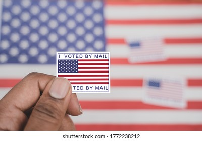 Holding I voted my mail sticker in hands with US flag as background - concept of voted through mail during election.