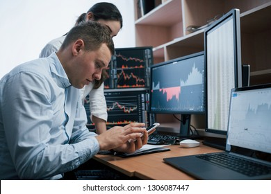 Holdng white smarphone and searching new information. Team of stockbrokers are having a conversation in a office with multiple display screens.