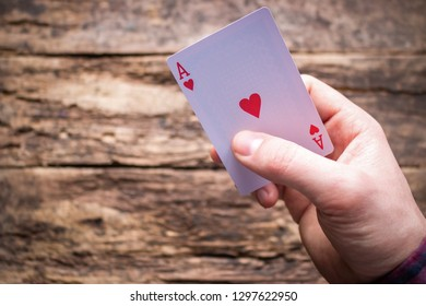 holds aces on a wooden background with space for text