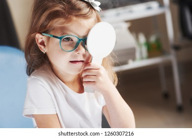Holds by herself the occluder. Little girl checking his vision with new green glasses.