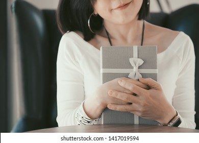 Holds a gift. Close up shot of female hands holding a small gift wrapped with white ribbon. Small gift in the hands of a woman indoor. Happy woman hold gift box.