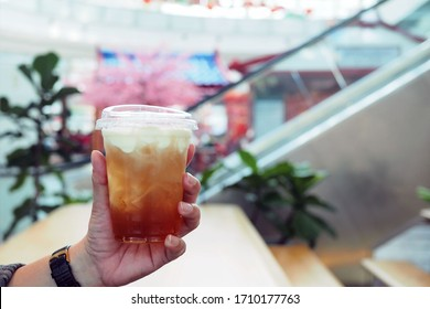 Holds a plastic glass of iced oolong tea (also called wulong or wu long) with layer of cream cheese foam on top, trendy Chinese beverage. Selective focus.