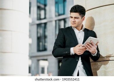 holds a tablet and writes a message. consultant business male employee works in a business center in a bank. the man is dark-haired of Indian appearance. business suit and white shirt. copy space.