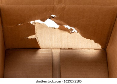hole in a cardboard box inside view close-up